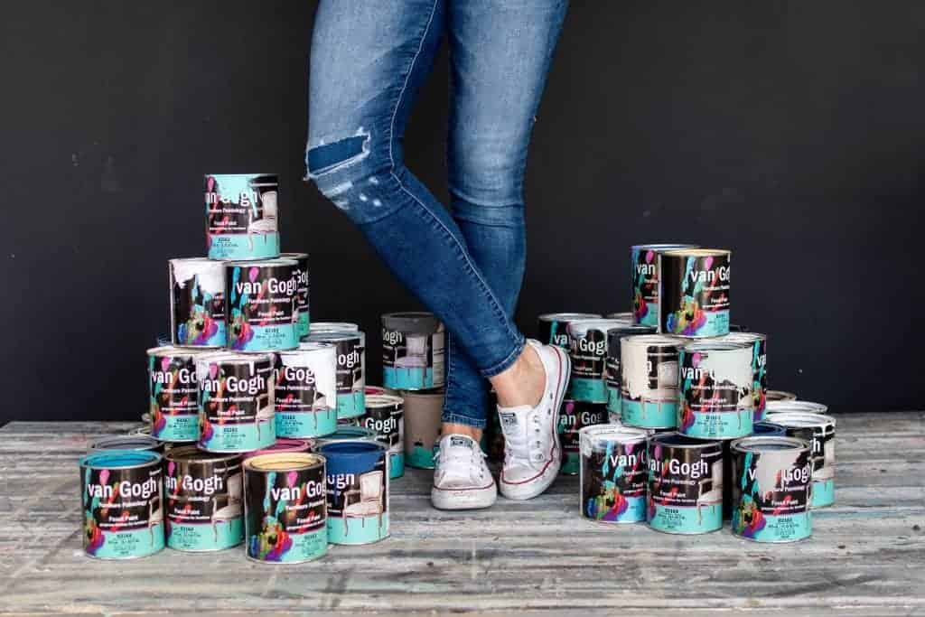 Collection of van Gogh Fossil paint cans surrounding the feet of Melanie Curley CEO of Mango Paint