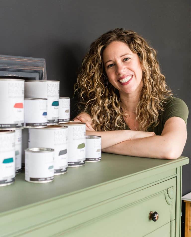 Melanie Curley CEO of Mango Paint invites you to fill out a retailer application while leaning on a painted dresser